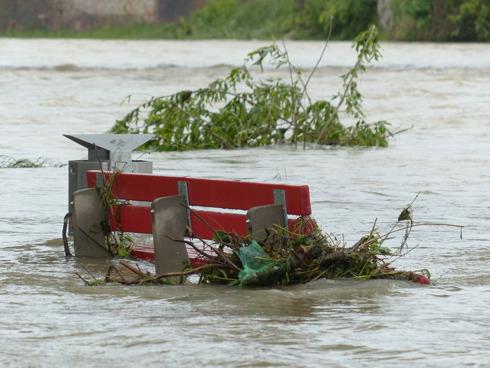 Panchina in un parco inondata dalla piena di un fiume
