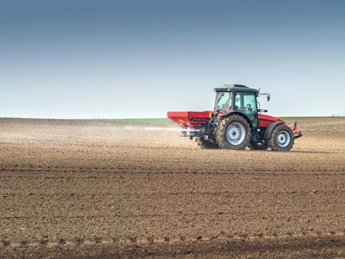 Fase di distribuzione fertilizzante a pieno campo con spandiconcime portato
