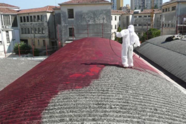 Operai che cospargono di liquido aggrappante la copertura in amianto di un capannone